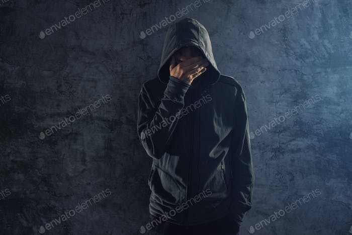 Depressed hooded person leaning on wall and crying