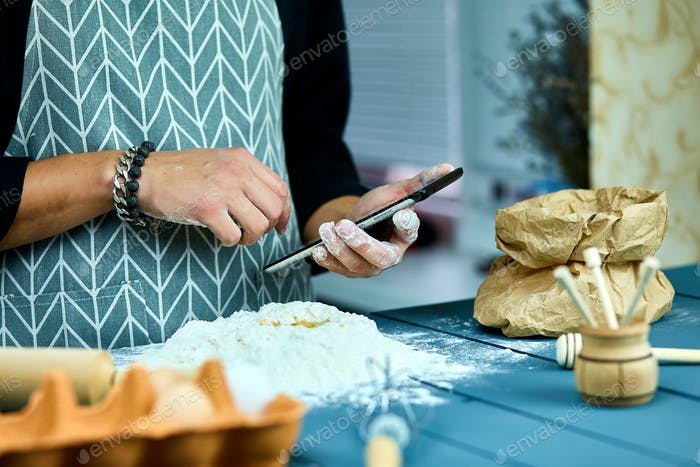 Man using electronic tablet pc in kitchen for baking.