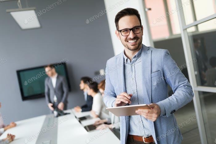 Portrait of handsome successful businessman holding tablet