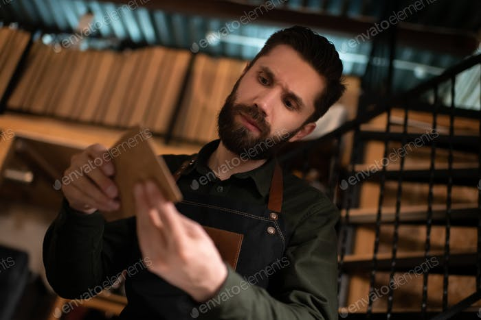 Male artisan examining leather handicraft