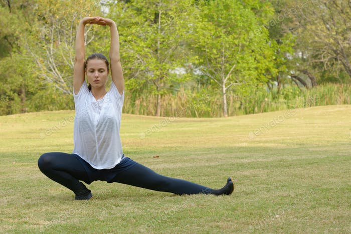 Young beautiful woman exercising at the park outdoors