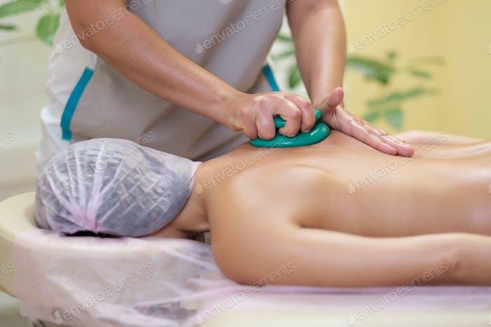 Massage therapist massaging young woman. Vacuum massage