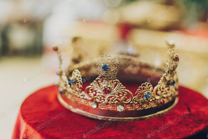 Christian golden crown for holy matrimony on red table in church