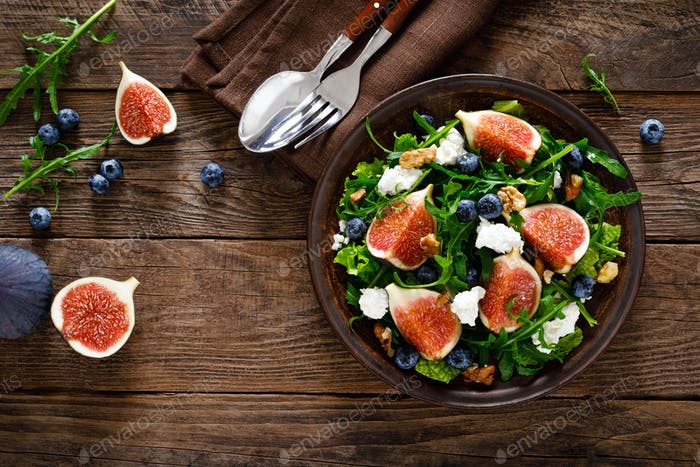 Fig salad with goat cheese, blueberry, walnuts and arugula on wooden background