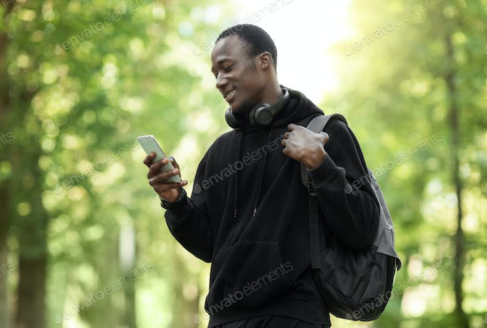 Happy african guy using smartphone, training at park
