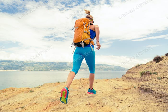 Woman running with backpack on rocky trail at seaside