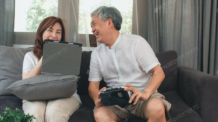 Asian elderly couple using tablet and virtual reality simulator playing games in living room.