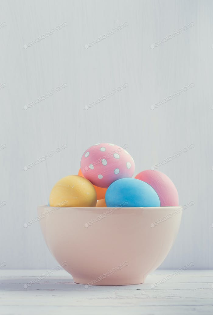 Bowl of colorful easter eggs with copy space