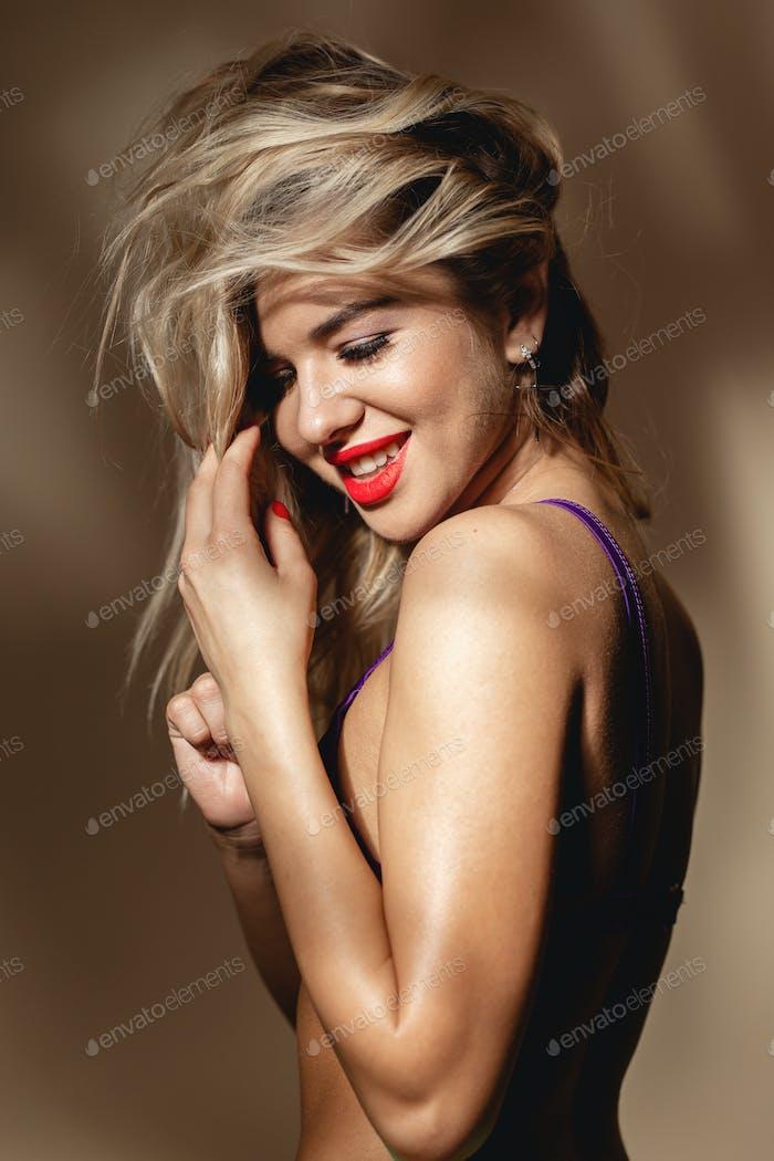 Blondes sexy Mädchen mit rotem Lippenstift in Badeanzug posiert gegen eine Wand mit Schatten im