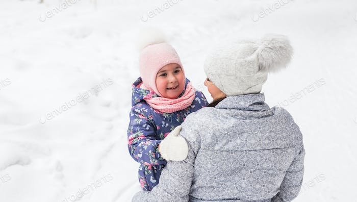 Family, children and nature concept - Young woman hug little happy daughter in the park