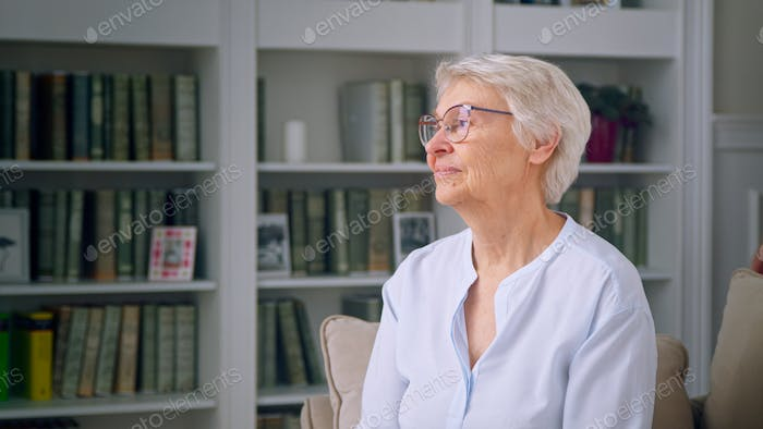 Portrait of the elderly woman in a white room