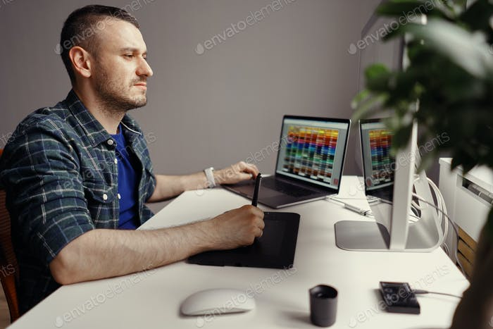 Modern man working remotely on a computer from home office