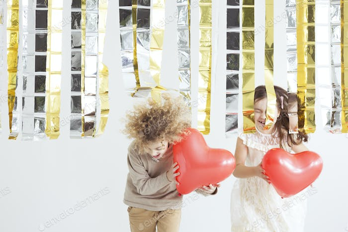 Little couple holding heart balloons