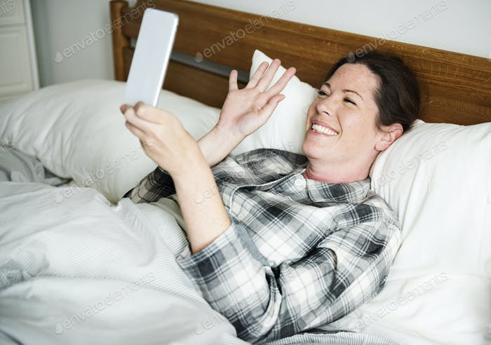 A woman video calling in bed