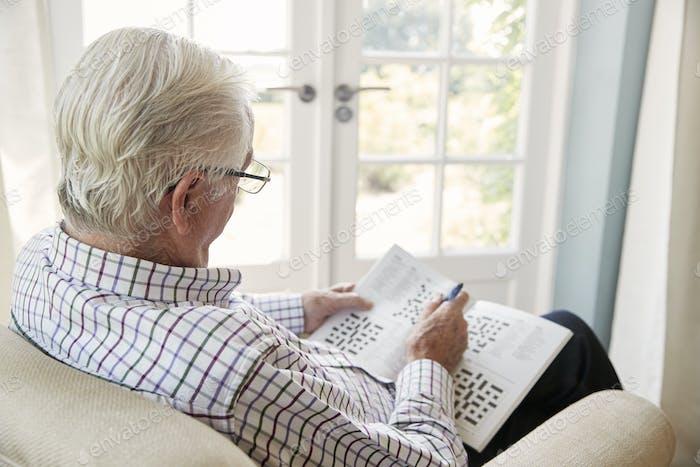 Senior man sitting in an armchair doing  crossword, close up