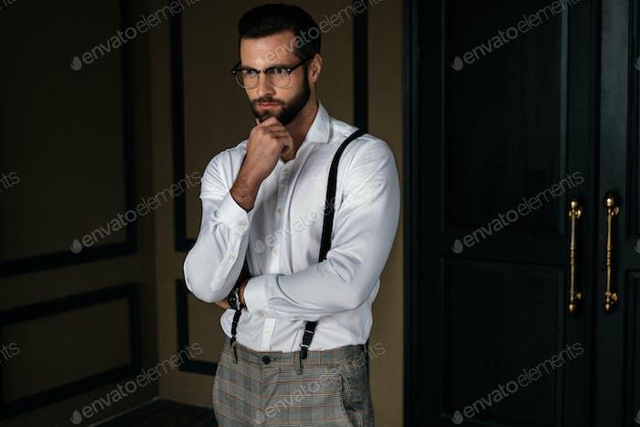 guapo barbudo hombre pensativo en camisa blanca y tirantes