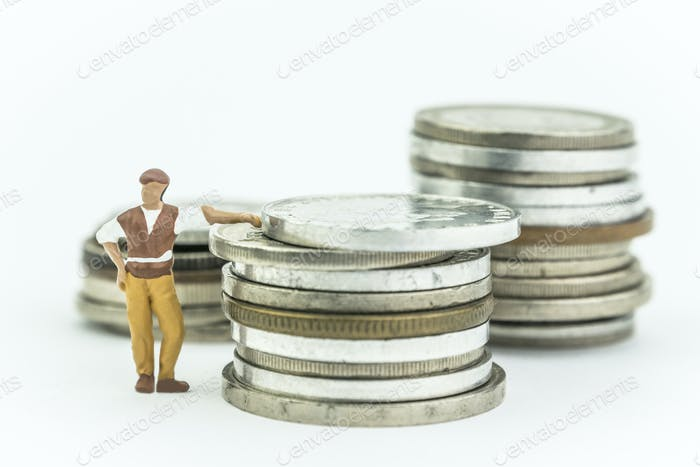 Miniature man next to a few coins, concept economy