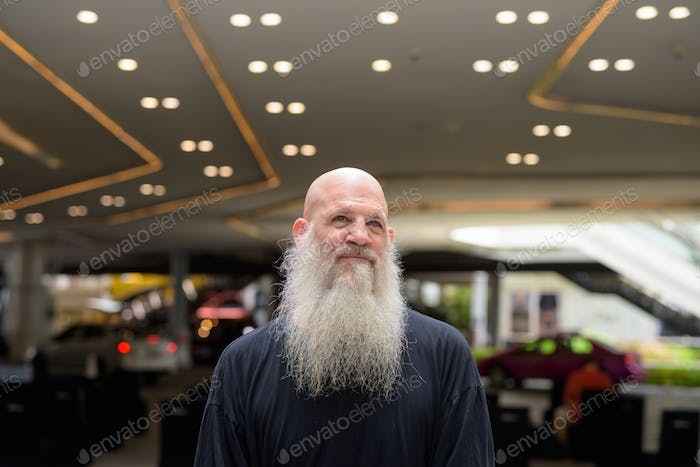 Mature handsome bald bearded man thinking in the city outdoors
