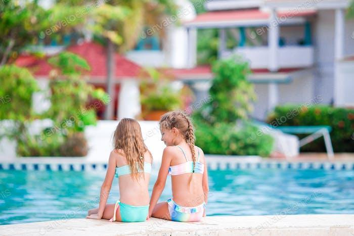 Entzückende kleine Mädchen im Außenpool im Urlaub