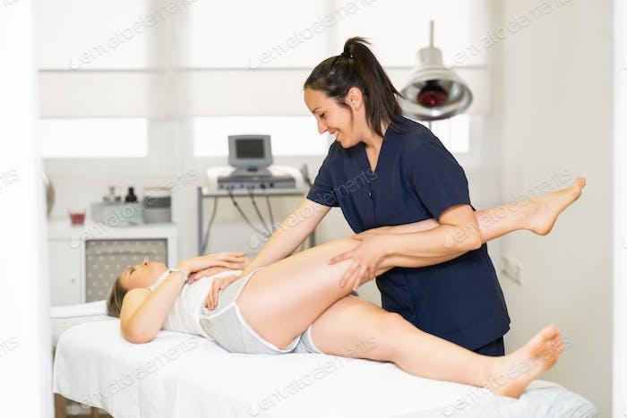 Physiotherapeutin inspiziert ihre Patientin in einem Physiotherapie-Zentrum