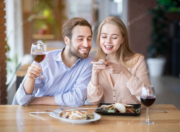 Affectionate millennial couple taking photo of yummy food and wine on smartphone at restaurant
