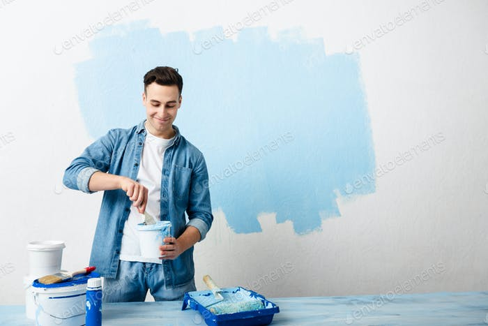 Happy guy mixes pigment for paint wall