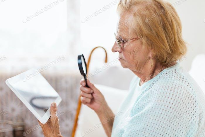 Ältere Frau mit Brille und Lupe mit einem digitalen Tablet