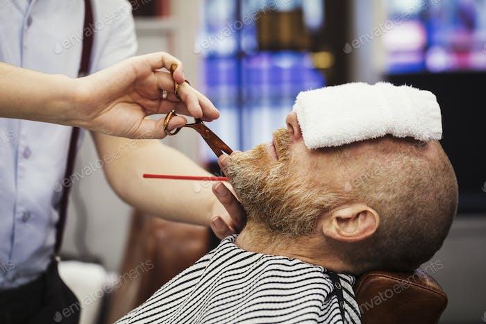 Ein Kunde sitzt auf dem Friseurstuhl, mit einem heißen Handtuch auf seinem Gesicht, und ein Friseur trimmt seine