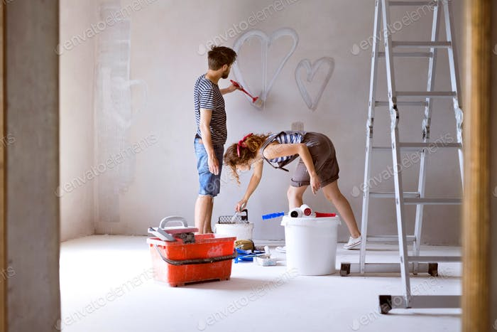 Couple painting hearts on the wall in their house.