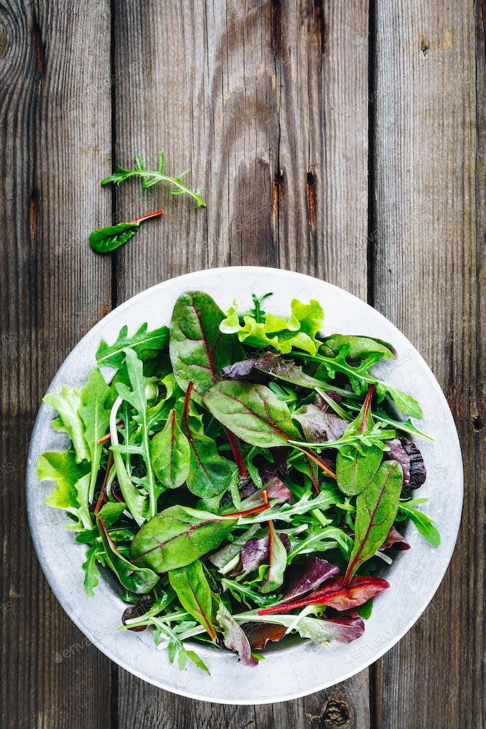 Mix of fresh leaves with arugula, lettuce, beets. Ingredients for salad on a wooden background.
