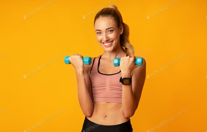 Cheerful Fit Girl Working Out With Dumbbells In Studio
