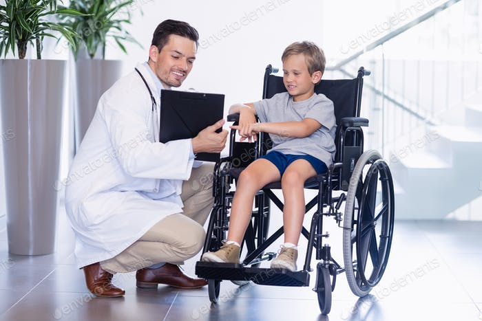 Doctor showing reports to disable boy in corridor