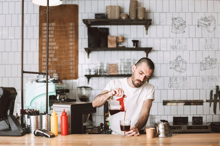 Young barista at bar counter dreamily pouring filter coffee in glass while working in cafe