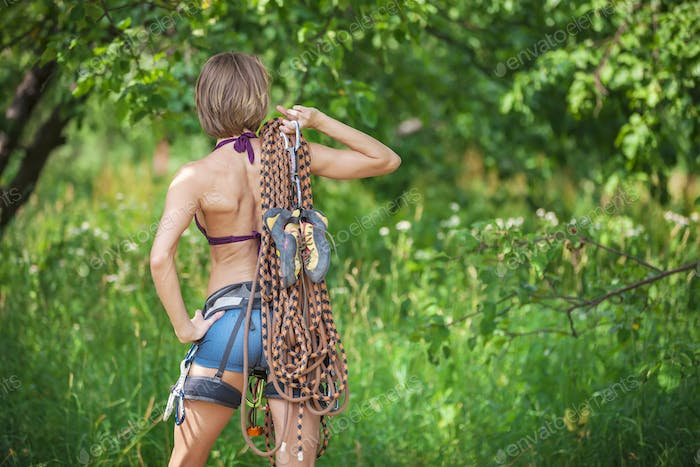 Rear view of young female rock climber posing outdoors