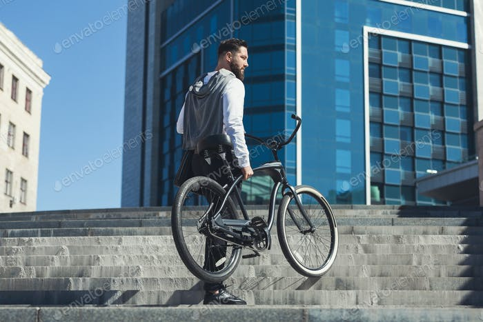 Bearded businessman carrying his bicycle on stairs