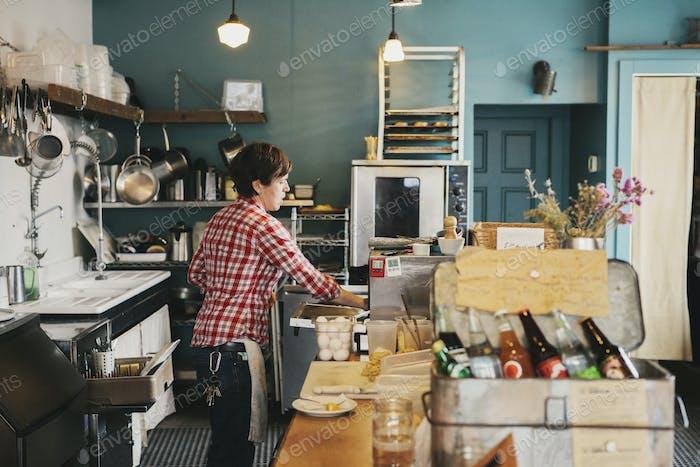 Eine Frau, die hinter der Theke in einem Café arbeitet.