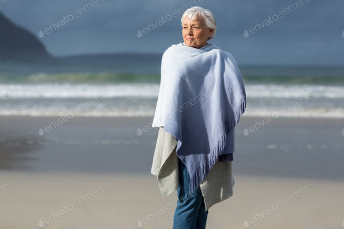 Senior woman wrapped in shawl at beach