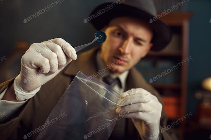 Männlicher Detektiv mit Pinzette findet Killerknopf
