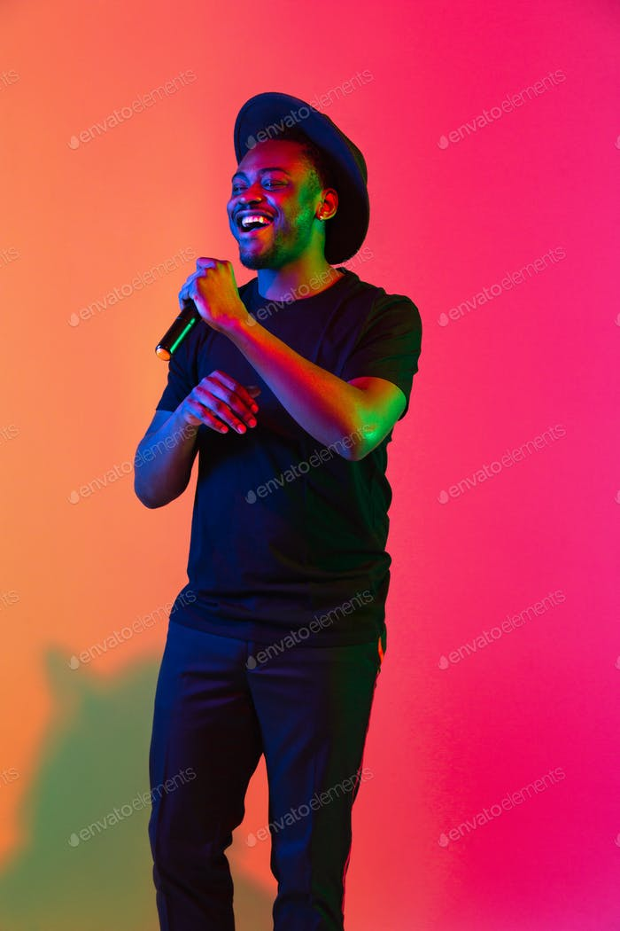Young african-american musician singing, dancing in neon light