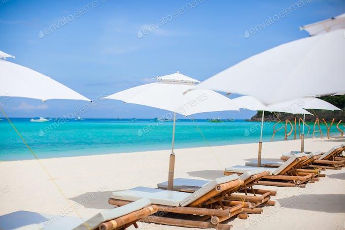 Beach chairs and umbrella on exotic tropical white sandy beach