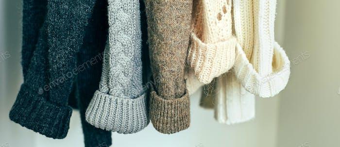 Gestrickte Kleidung Pullover hängen im Schrank. Gemütliche Herbst-Winter-Garderobe Banner Bild