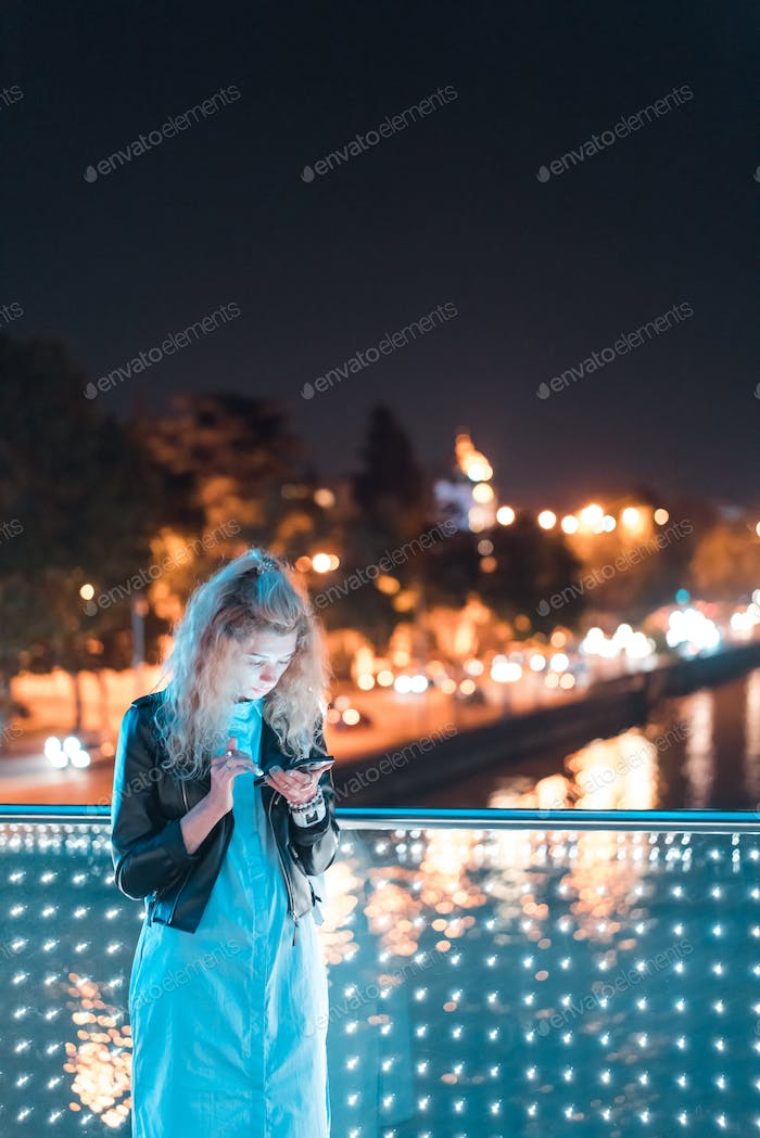 Girl with a smartphone on a bridge