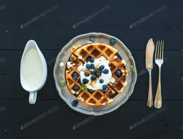 Soft Belgian waffles with blueberries, honey and whipped cream on vintage metal plate
