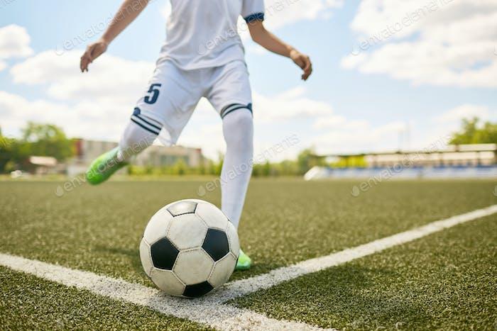 Boy Kicking Ball on Football Field