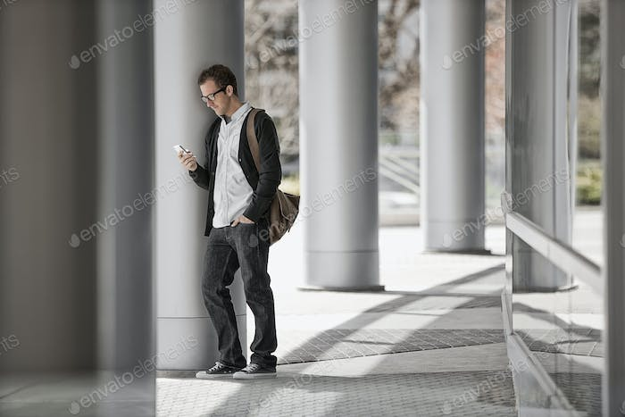 A man outside a building, checking his smart phone.