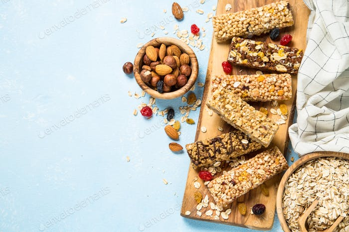 Granola bar with nuts, fruits and berries on blue