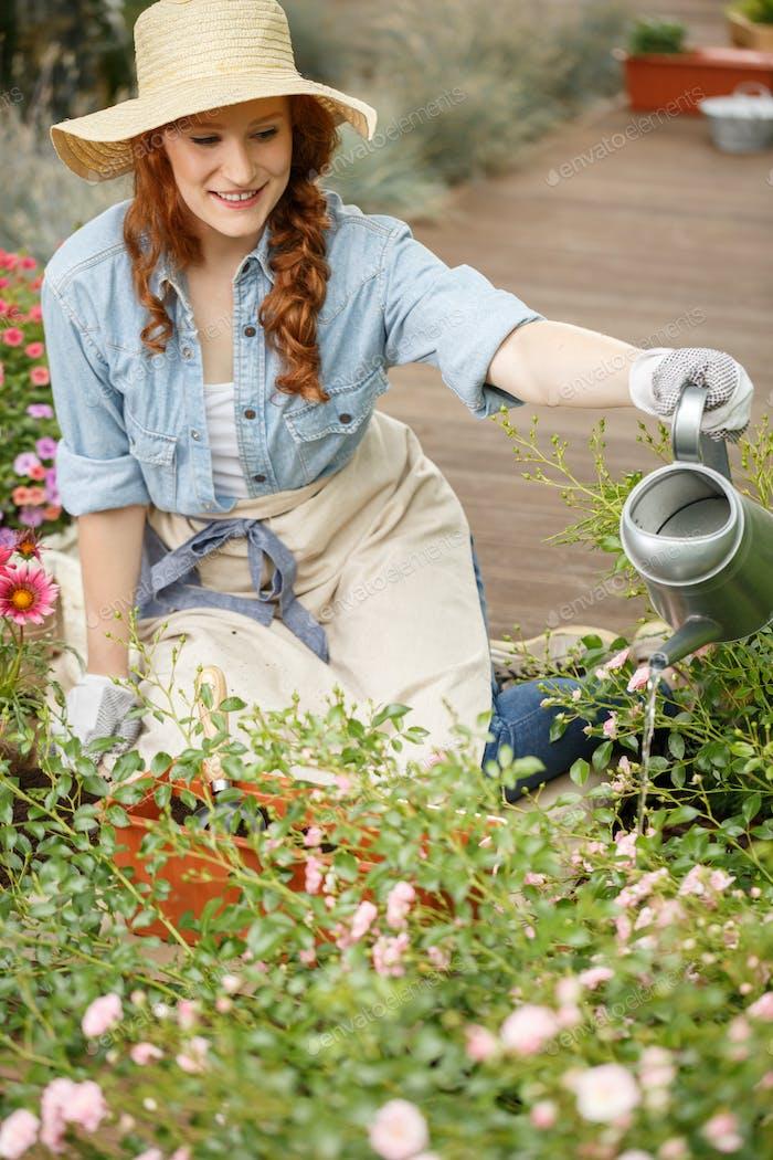 Smiling gardener woman watering flowers