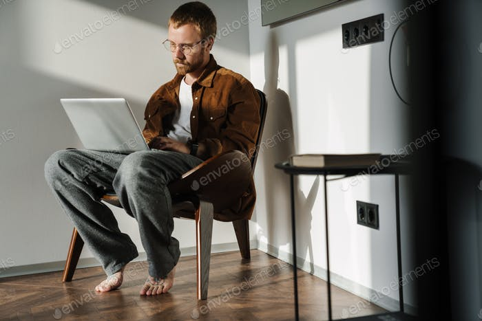 Photo of young man working with laptop while sitting in armchair