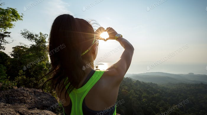 Sporty woman making heartshape with sunset sunlight rays on seaside mountain top