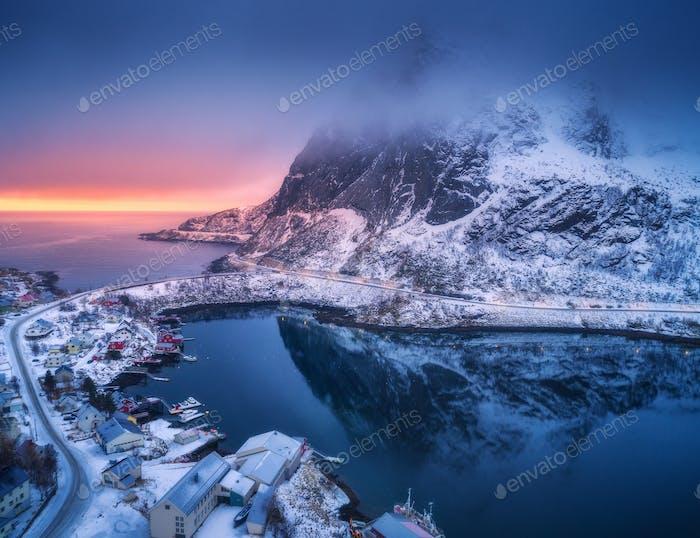 Luftaufnahme von verschneiten Berg, Dorf an der Küste, bunten Himmel